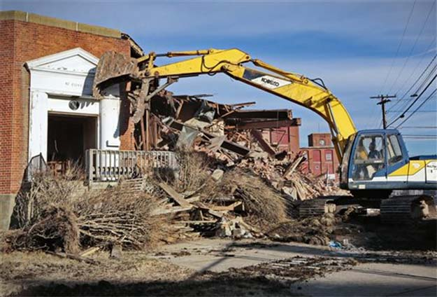 An excavator operator demolishes the entrance to the former headquarters of the Berkshire Hathaway mill (Photo: AP)