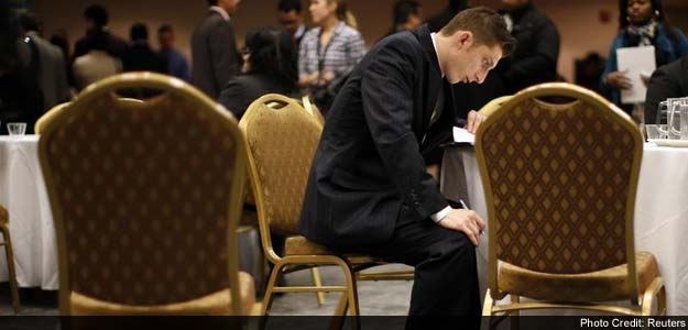 A job seeker fills out forms at a table while attending a career fair with prospective employers in New York City