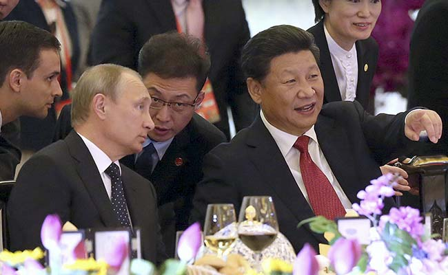 President Xi Jinping (front R) speaks to Russian President Vladimir Putin (front L) during a welcome dinner. (Reuters)