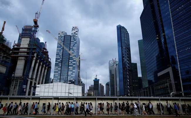 Office workers walk to the train station during evening rush hour in the financial district of Singapore.