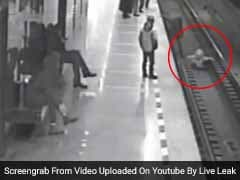 Thrilling Footage Shows Man Jumping On Train Tracks To Save Little Boy