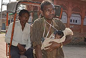 This rickshaw puller has a child strapped to his chest