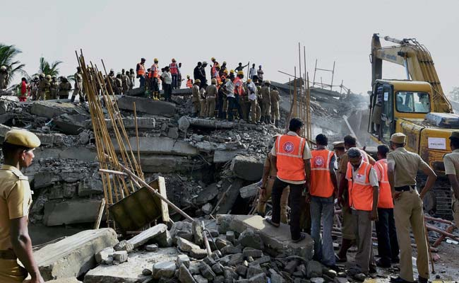 Workers and policemen at the collapsed 11 storey building on sunday