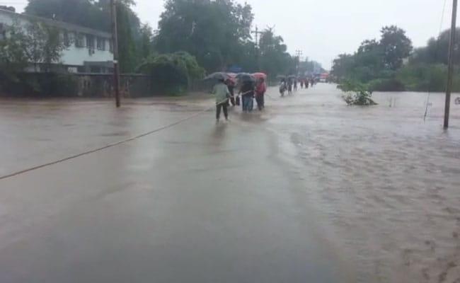 मुंबई से सटे पालघर में भारी बारिश के बाद लोगों को रस्सी के सहारे पार करनी पड़ी सड़क