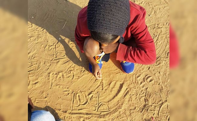 child writing on sand