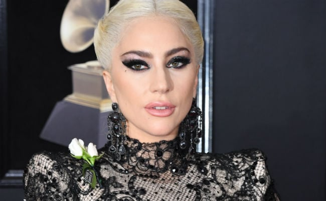 Stars don white roses at Grammys red carpet