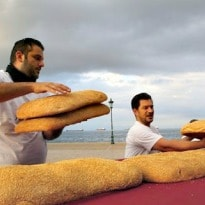 Greek Bakers Encircle Monument With Ring Bread